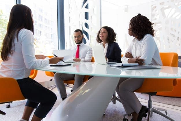Questions to ask during informational interview consulting. Image shows a team of people meeting around a conference table.