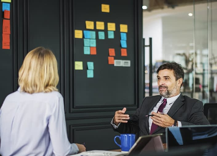 consulting behavioral interviews. Image depicts a man and a woman having a business conversation.
