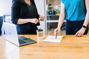 two women standing over a table reviewing paperwork
